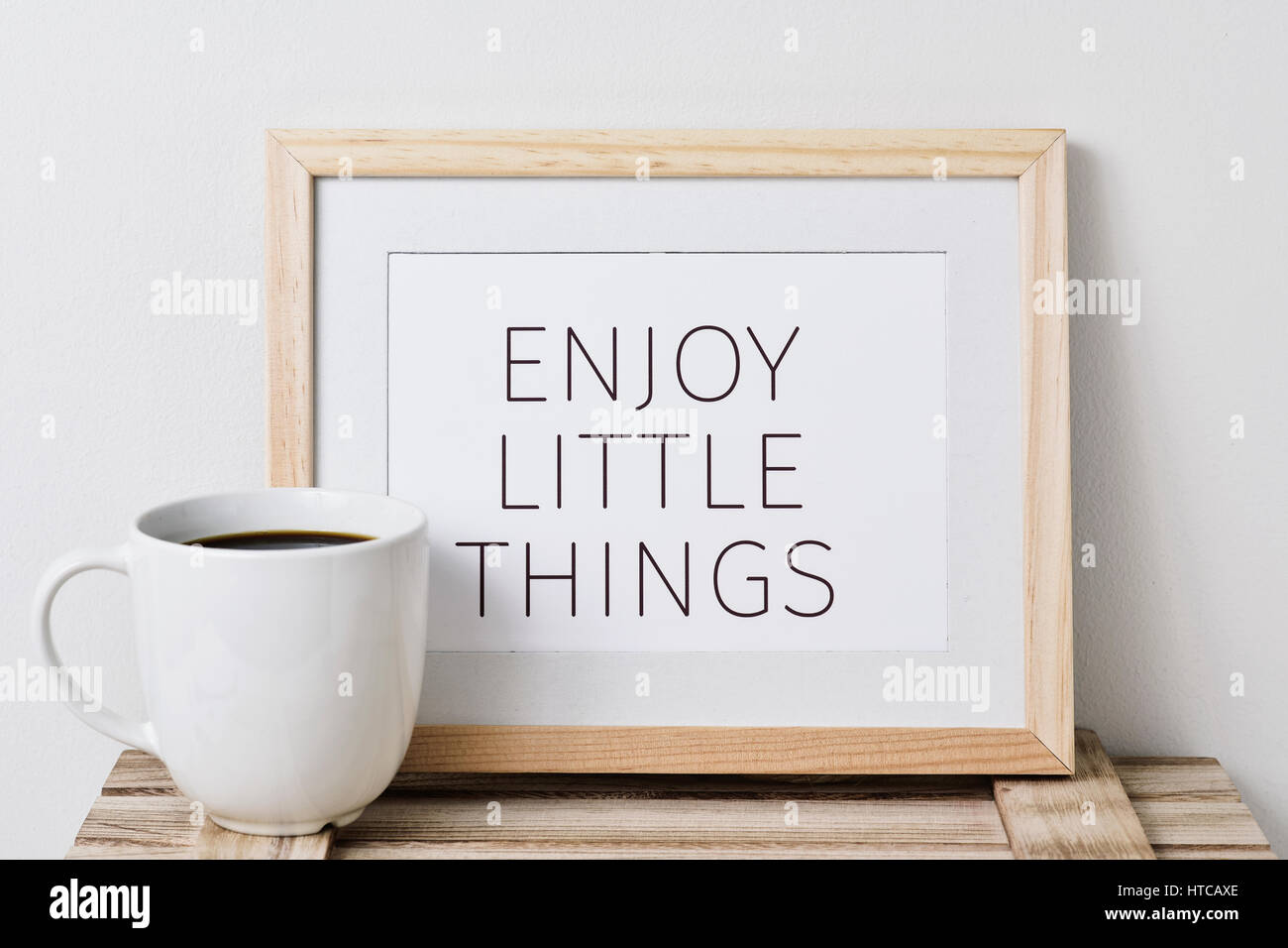 a wooden-framed picture with the text enjoy little things written in it and a cup of coffee, on a rustic wooden - Stock Image