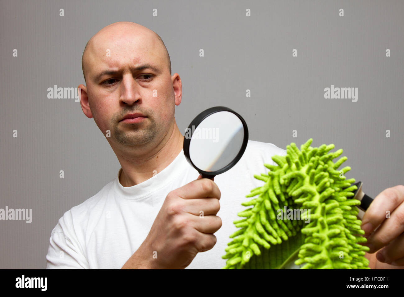 The guy is considering a magnifying glass green doormat - Stock Image