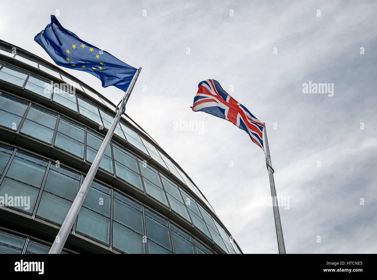 Looking up at EU and UK flags blowing in the wind outside City Hall, London Stock Photo