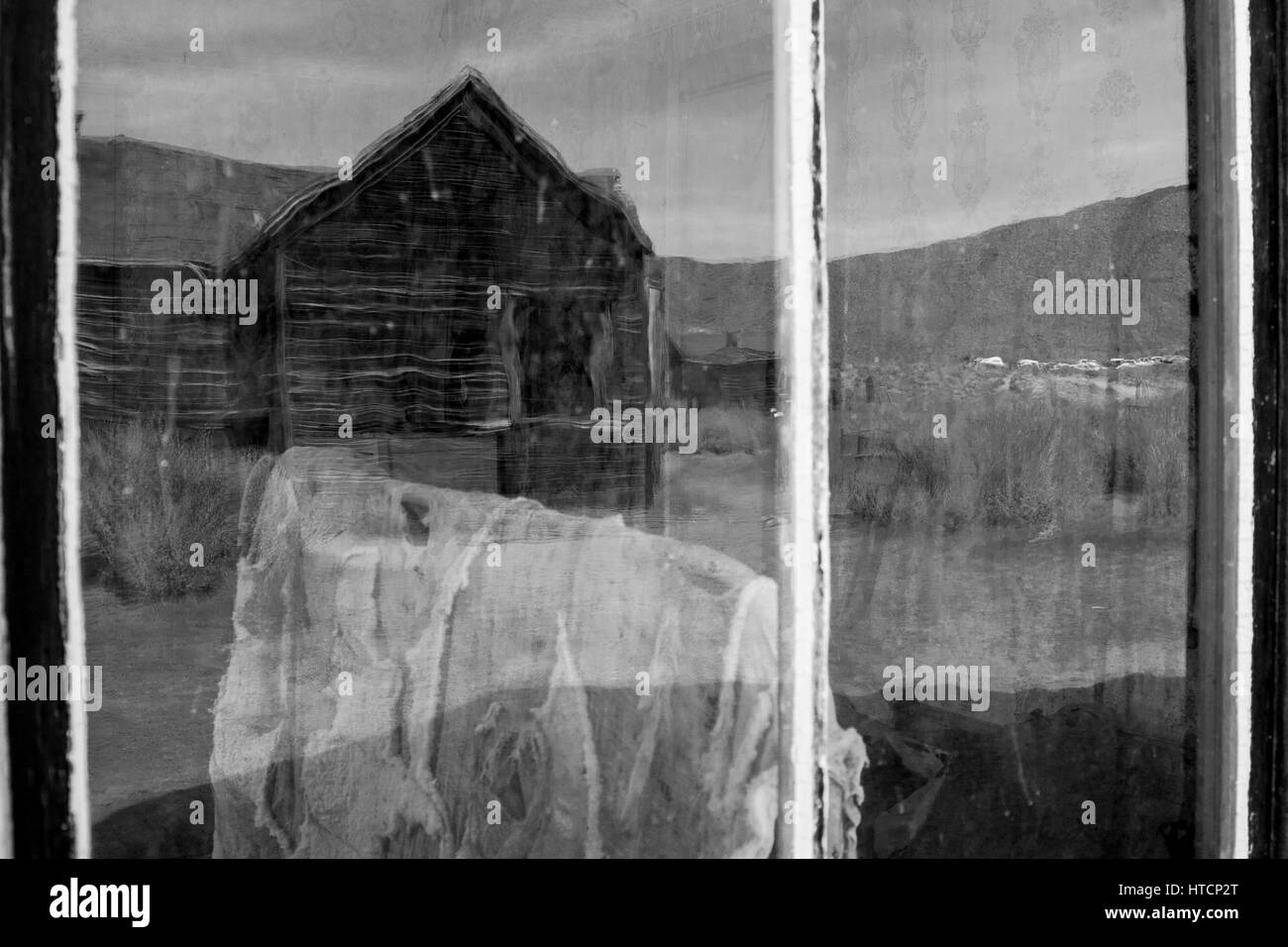 A reflection in the window in Bodie. The Bodie State Park is the remains of Bodie, a silver and copper mining town Stock Photo