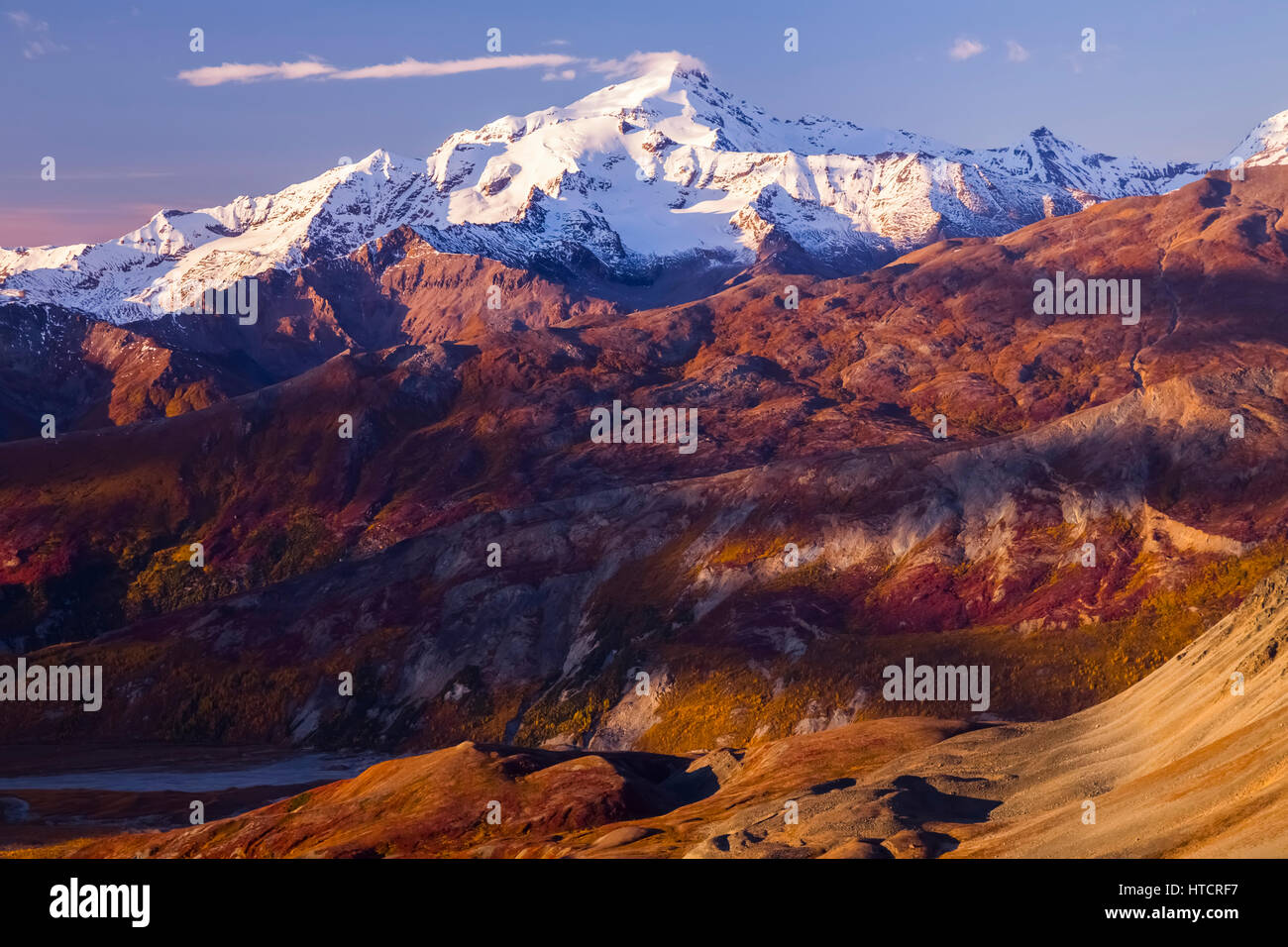 The sun sets on Mt. Silvertip in the Alaska Range with fall colors on the landscape below, Interior Alaska, USA - Stock Image
