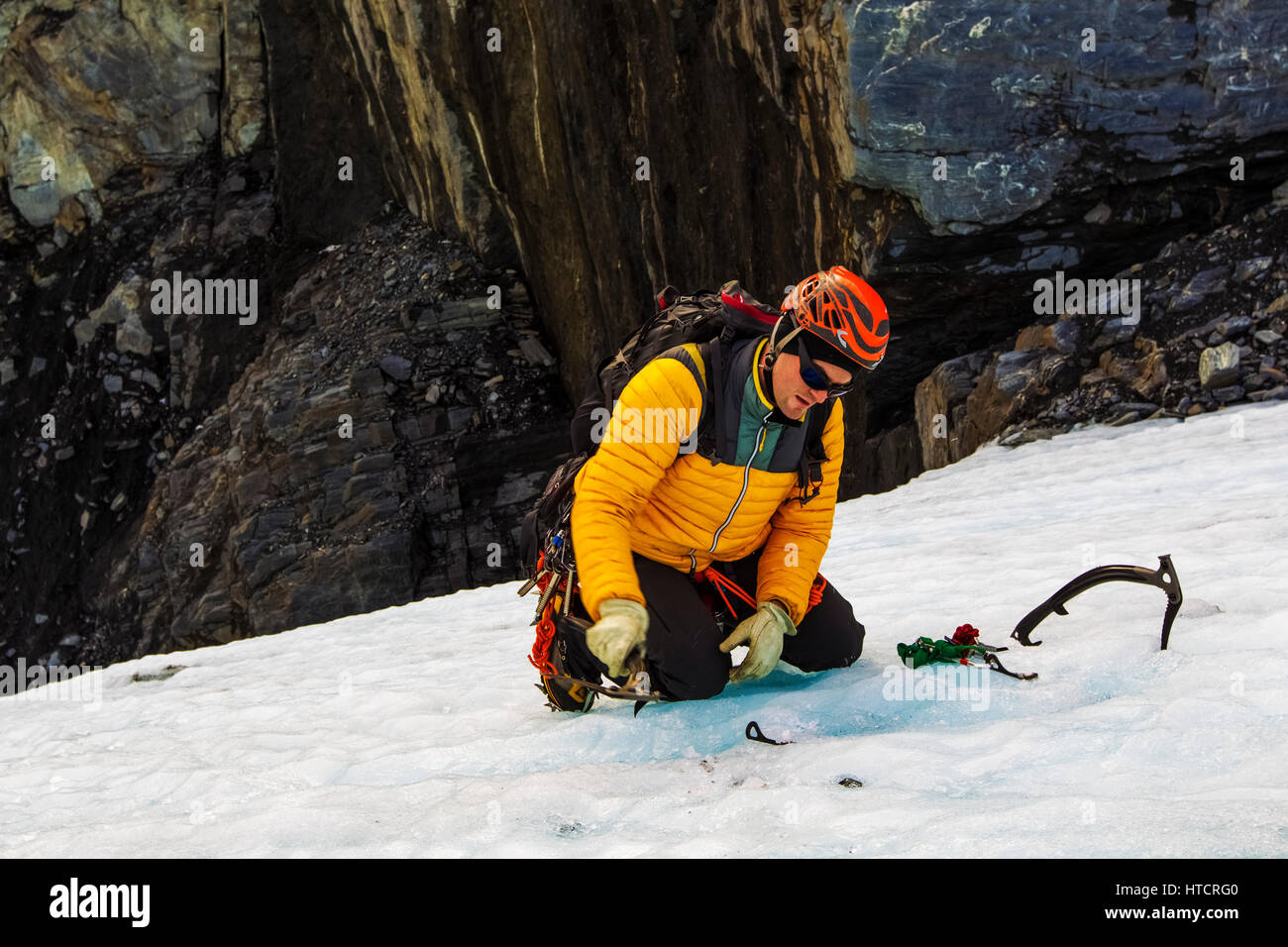 A climber places ice screws when setting up an anchor for rappelling in to a crevasse in Worthington Glacier, Southcentral - Stock Image