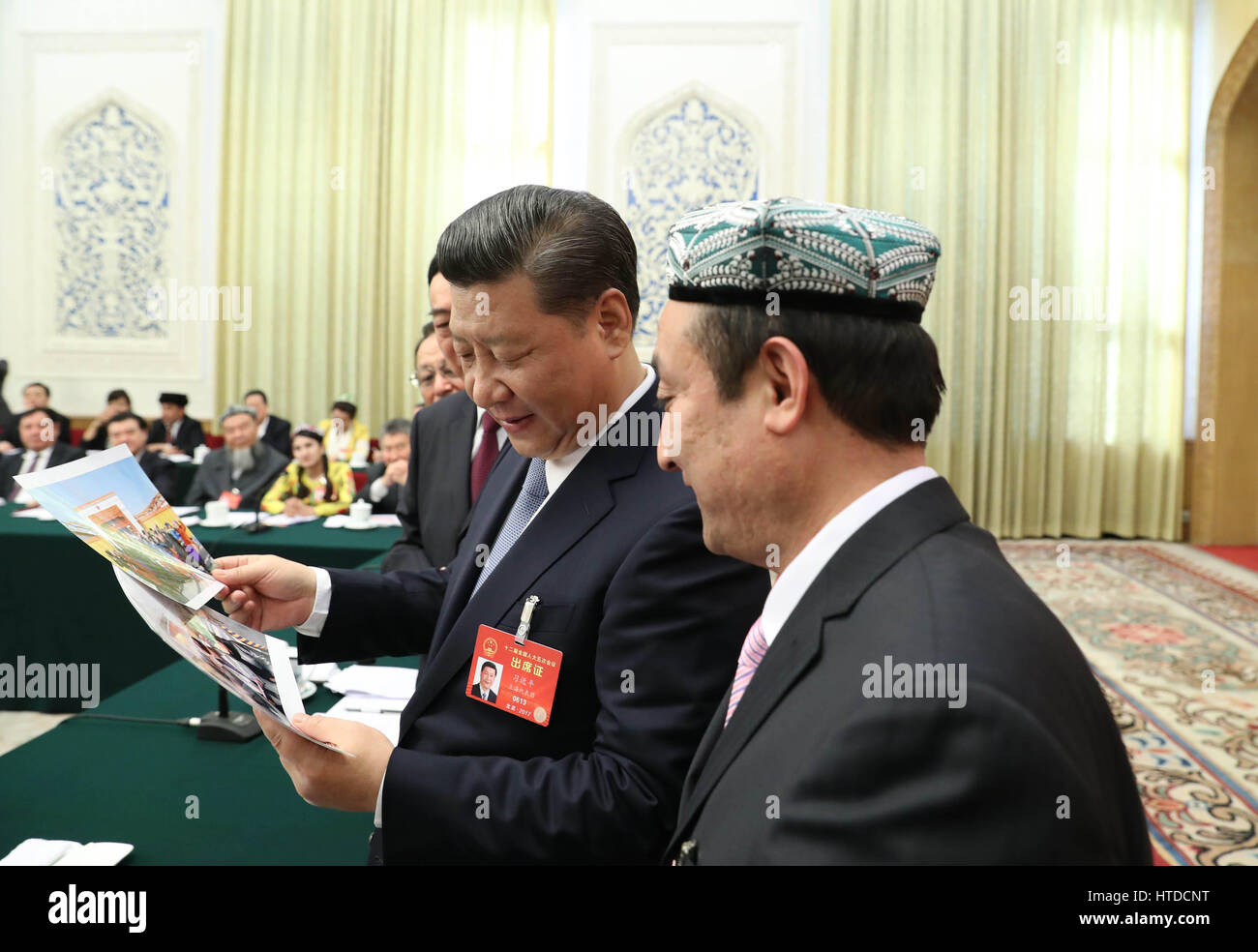 Beijing, China. 10th Mar, 2017. Chinese President Xi Jinping looks at photos of the family of Kurban Tulum when - Stock Image