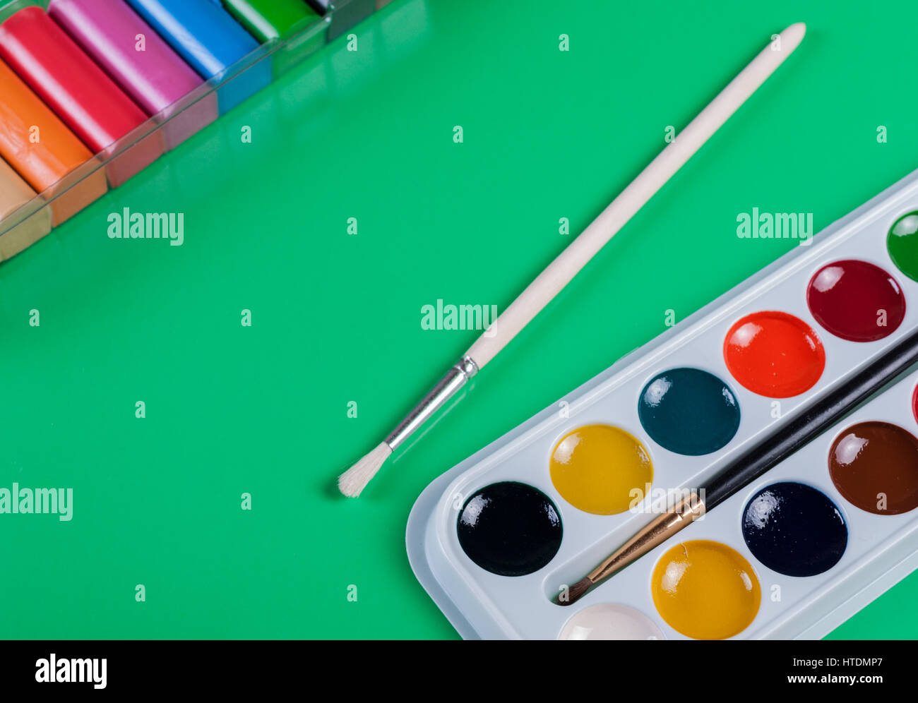 Watercolor paints and plasticine on a green background. For children's creativity - Stock Image