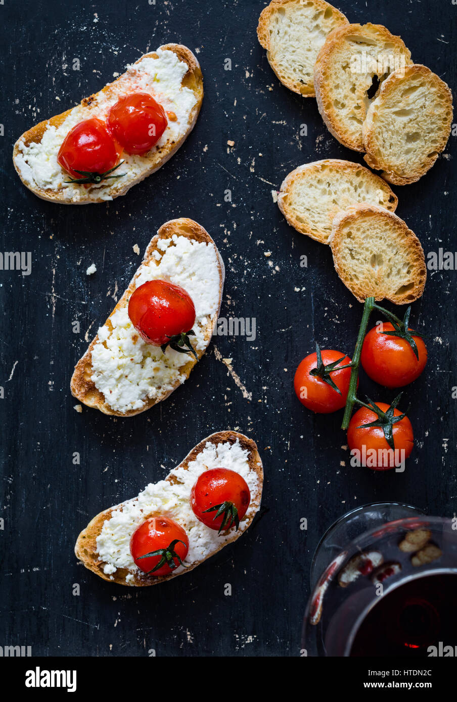 Toast with white cheese spread and roasted cherry tomatoes and glass of red wine over black background. Top view - Stock Image