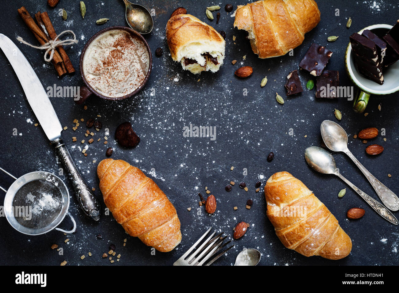 Coffee, croissants, chocolate, spices, nuts and vintage cutlery. Flat lay composition of sweet breakfast food on - Stock Image