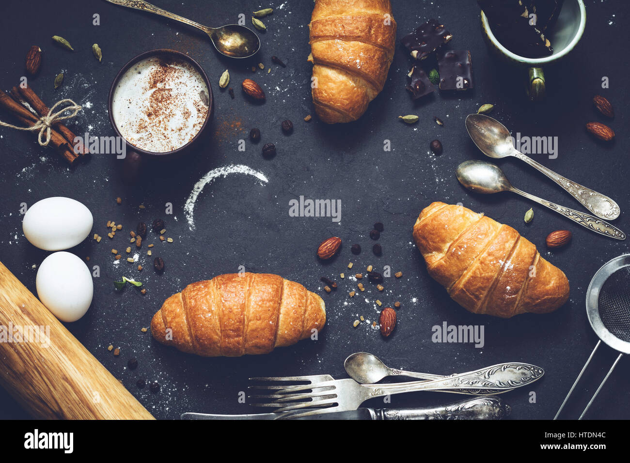 Coffee, croissants, chocolate, spices, nuts and vintage cutlery. Flat lay composition of sweet breakfast food on Stock Photo