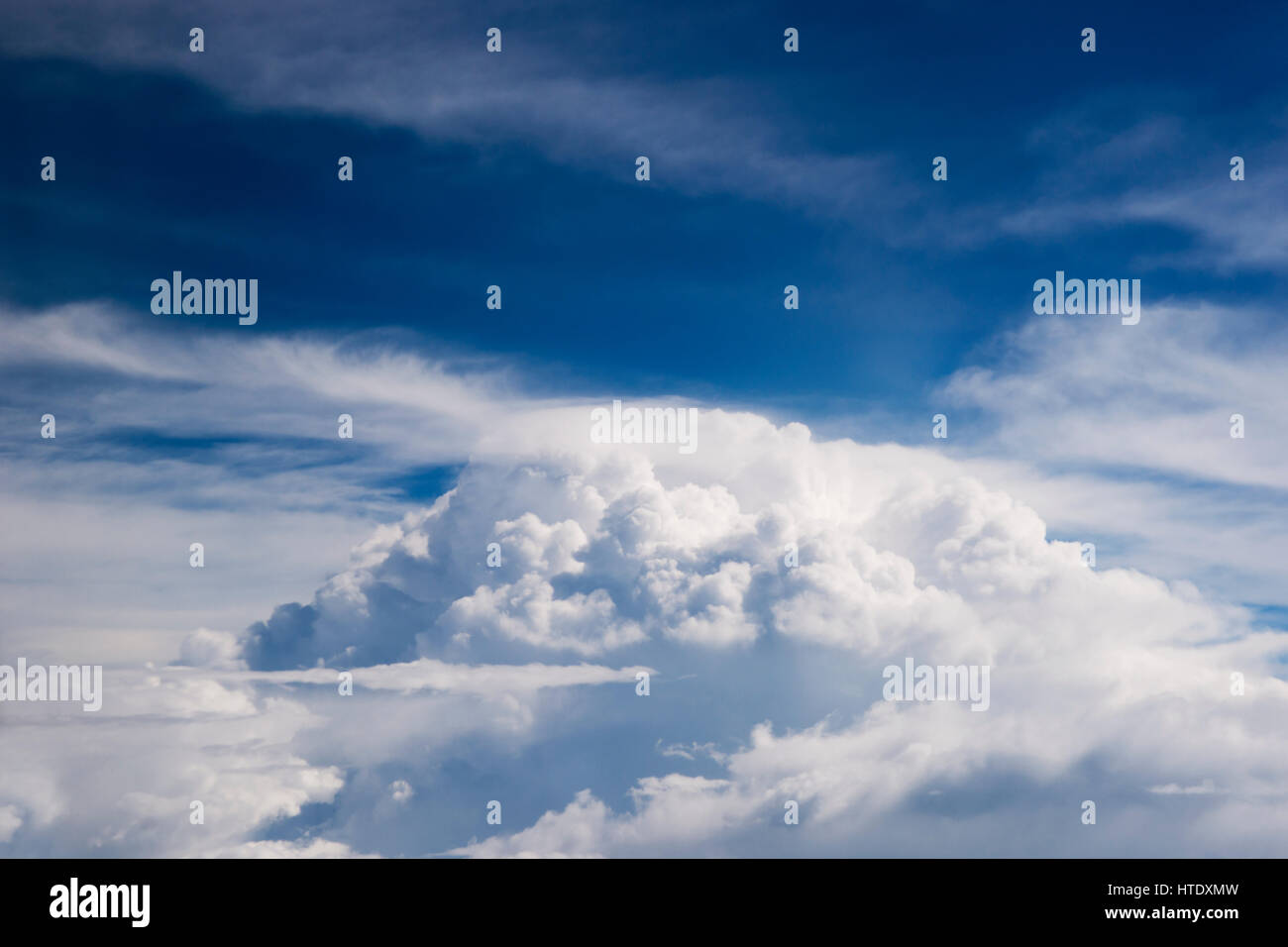 Airplane window seat view of big white thick fluffy clouds with a clear blue sky at the background in the afternoon. - Stock Image