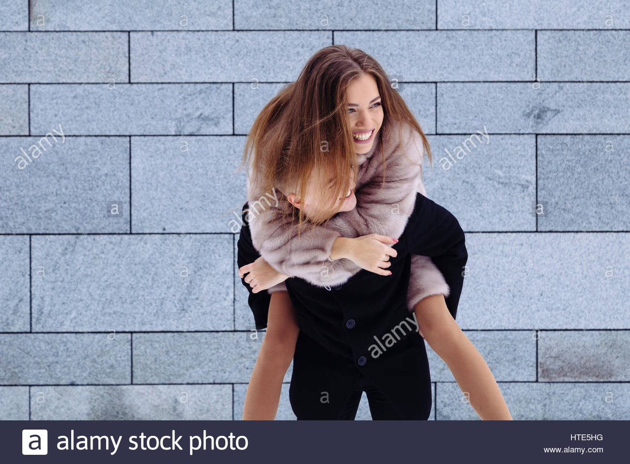 Portrait of a handsome man piggybacking his girlfriend on a vacation. - Stock Image