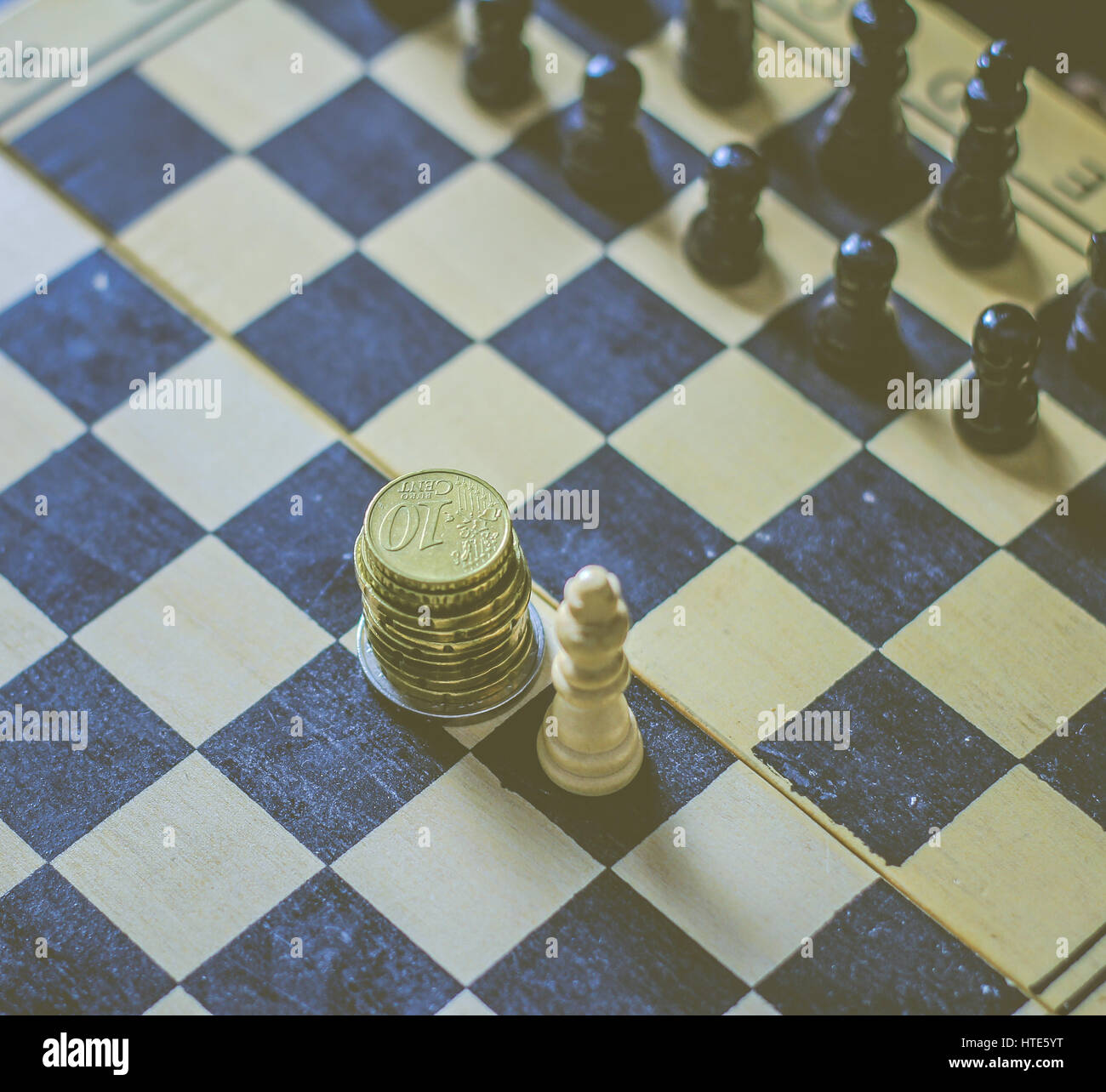 Picture Of A Chess Board With Stack Of Coins As The King Stock Photo