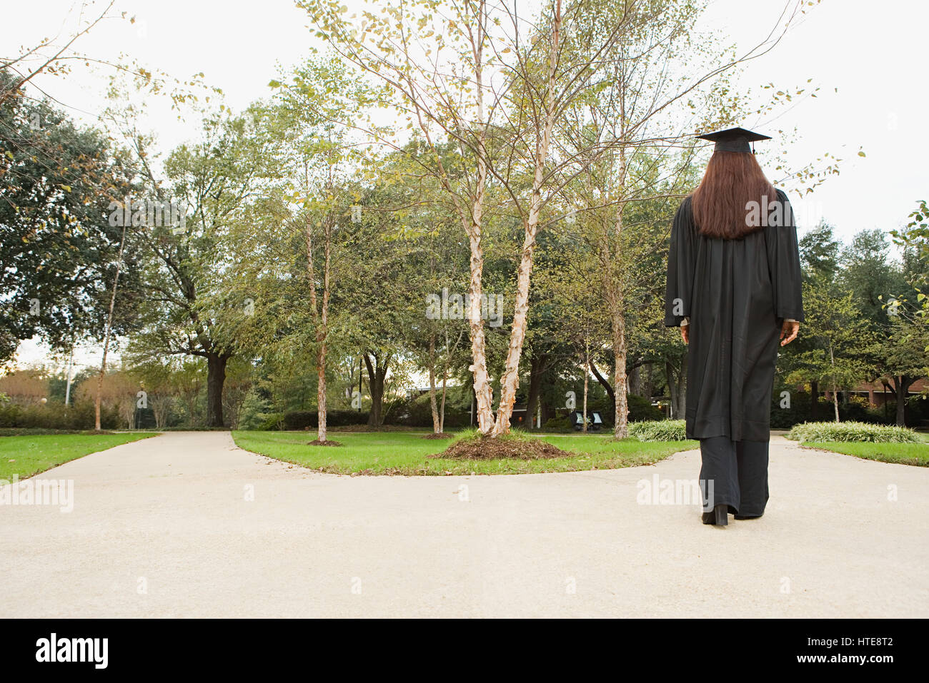 Female graduate walking down a path - Stock Image