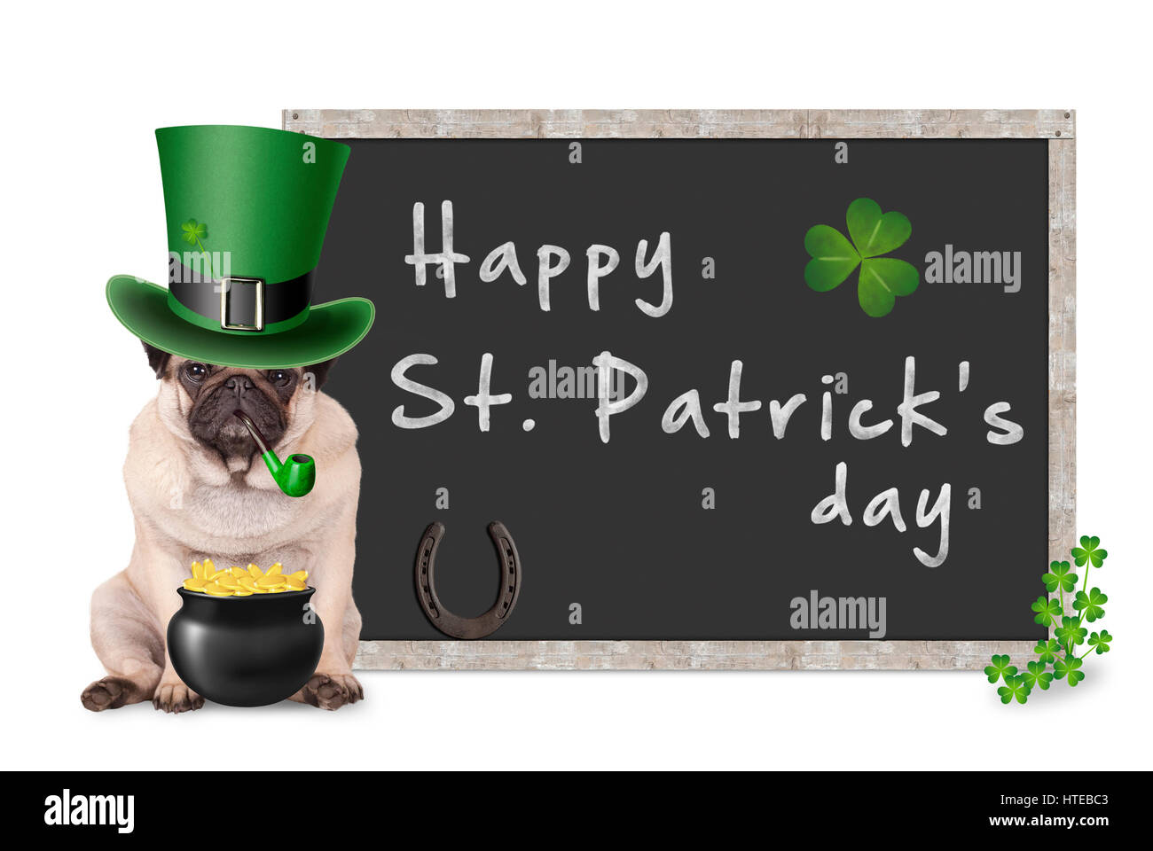 cute pug puppy dog with leprechaun hat for st. patrick's day smoking pipe, sitting next to blank blackboard sign Stock Photo
