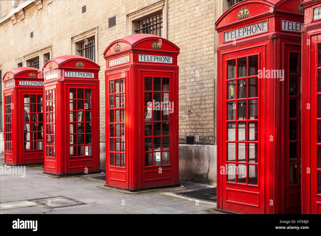 A row of red telephone boxes in London. - Stock Image