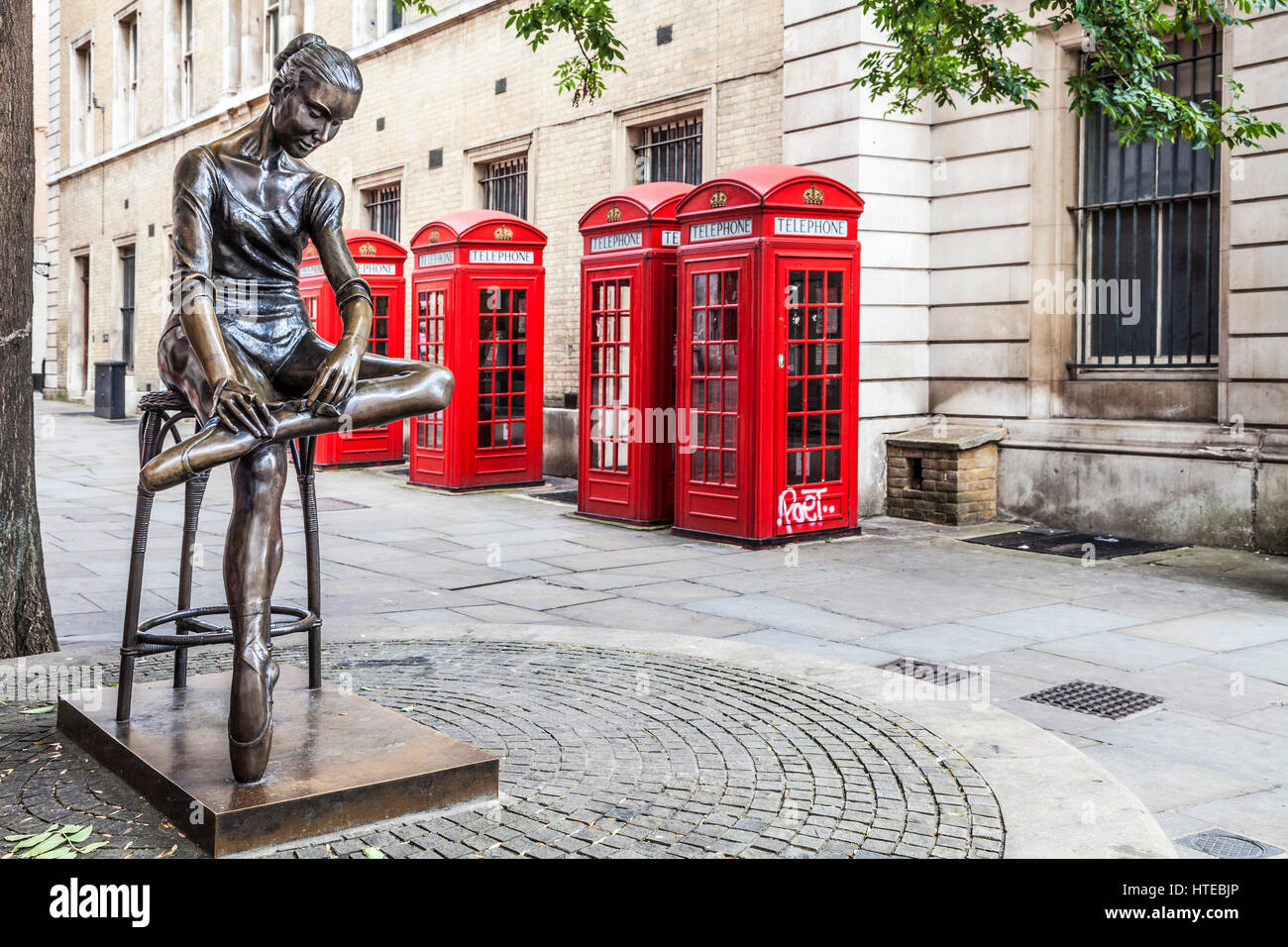 Statue of a young dancer by Enzo Plazzotta with a row of red telephone boxes in London. - Stock Image