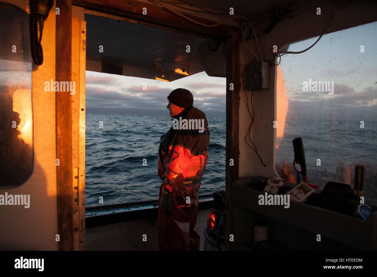 Lobsterman takes in the view after a long 14 hour day - Stock Image