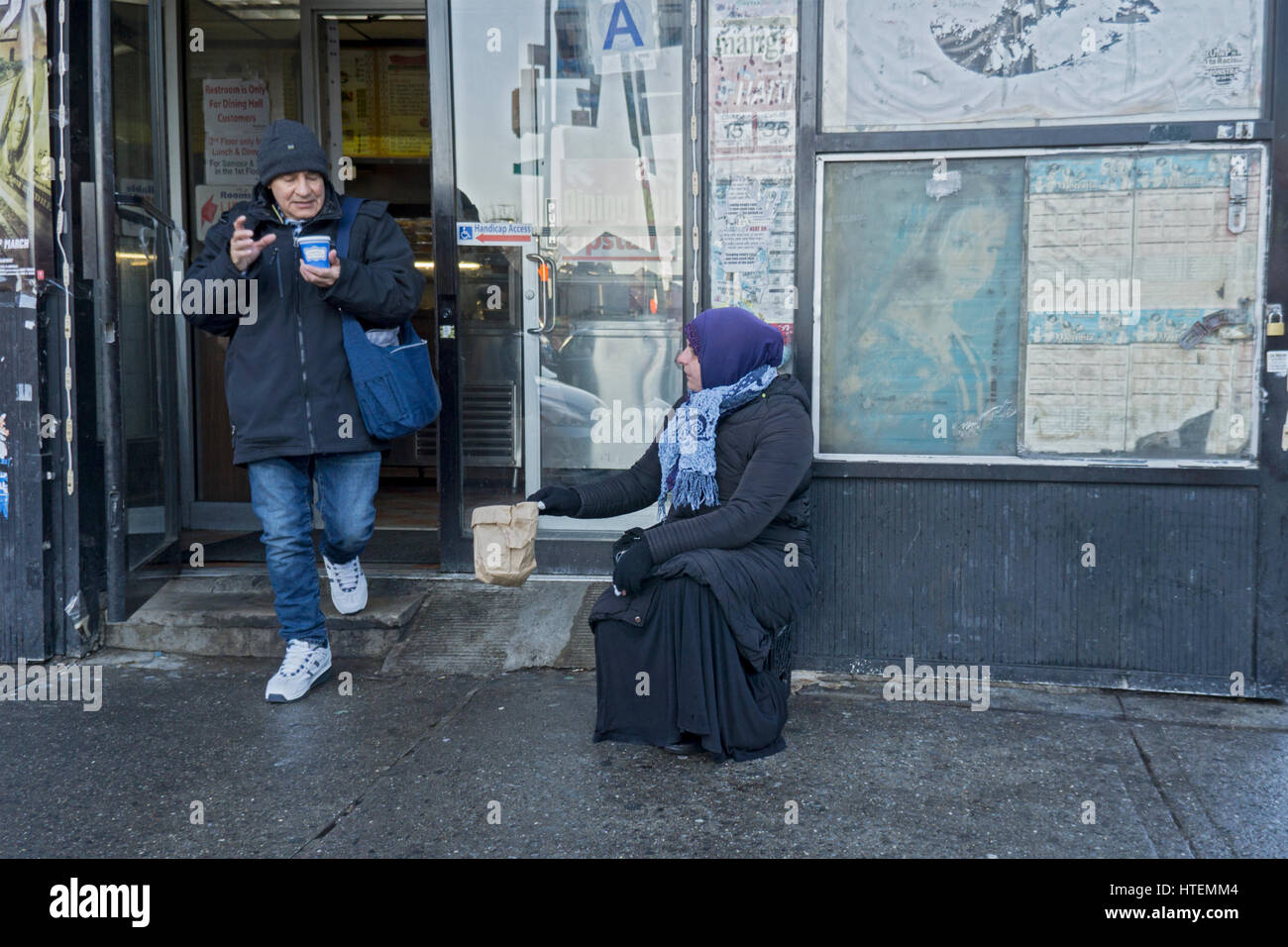 A poor Muslim woman asking for donations outside a food shop in Jackson Heights, Queens, New York City. - Stock Image
