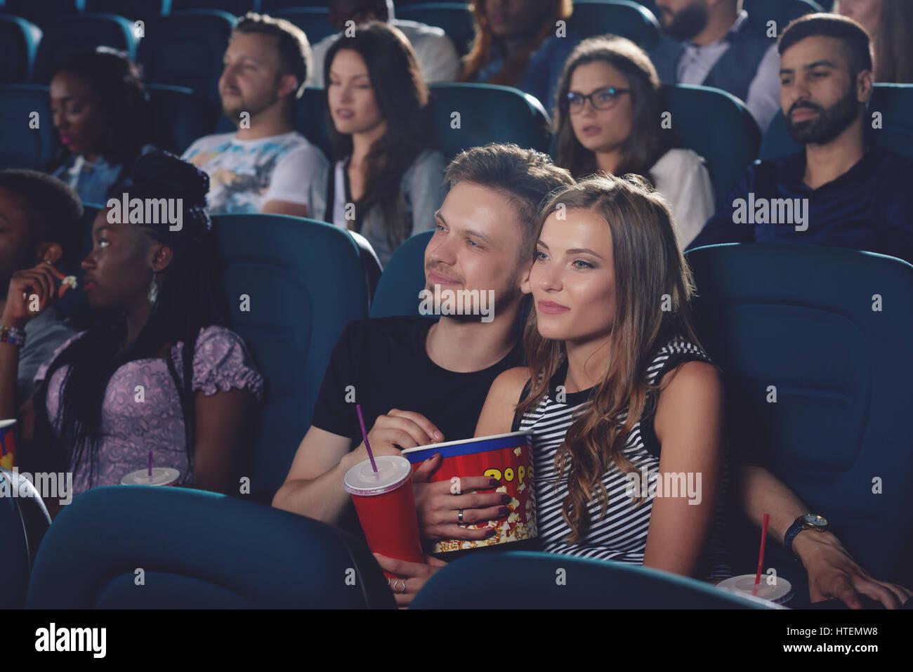 handsome boyfriend and pretty blonde girlfriend watching movie and