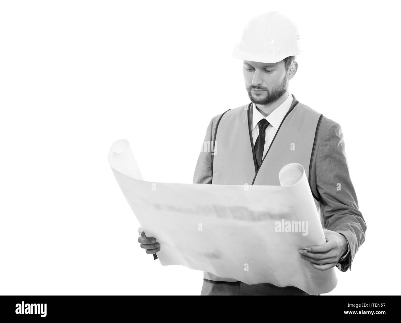 Final check. Black and white shot of a confident successful male constructionist in a hardhat and safety vest looking - Stock Image