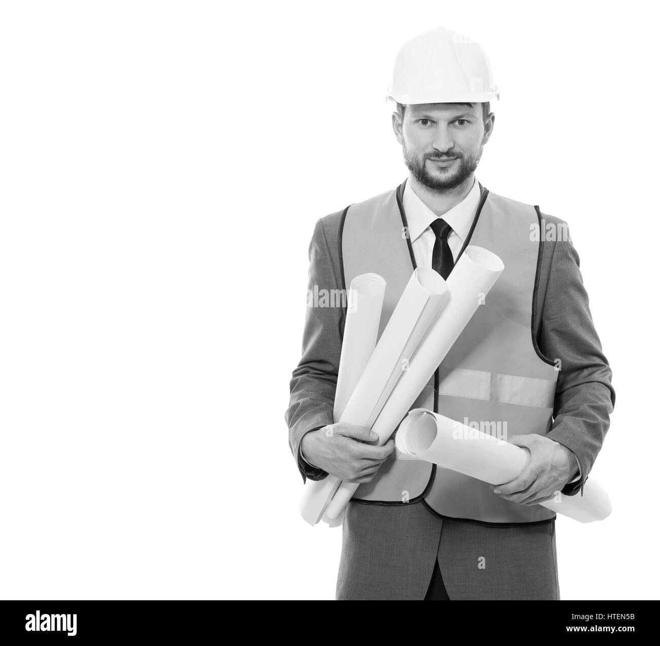 Developing business. Vertical studio portrait of a cheerful male engineer in a hardhat and safety vest posing on - Stock Image