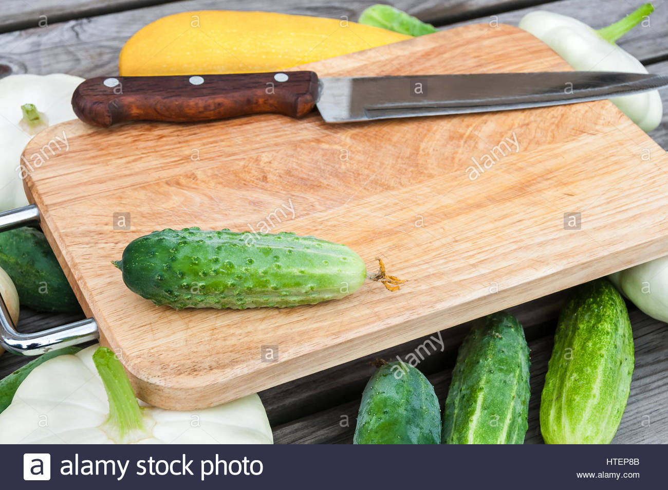 Cutting board, knife, fresh vegetables on wooden table.  Top view with copy space. - Stock Image