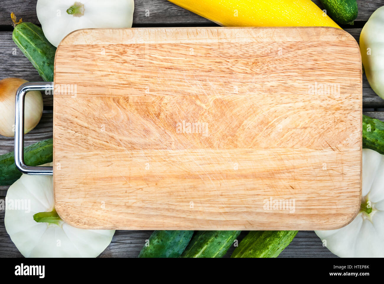 Cutting board, fresh vegetables on wooden table.  Top view with copy space. - Stock Image