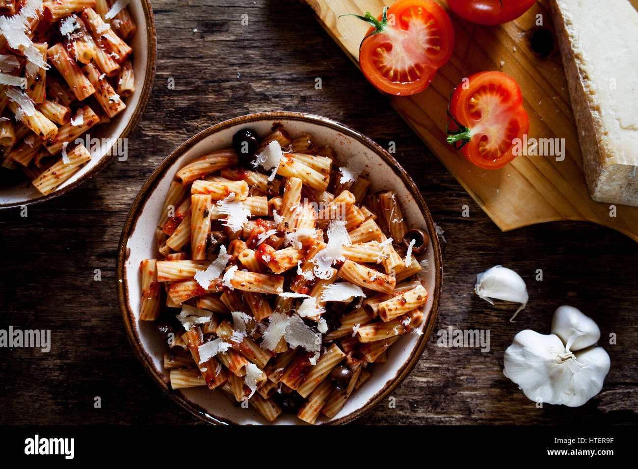 Couple of plates of rigatoni pasta with tomato sauce and olives - Stock Image