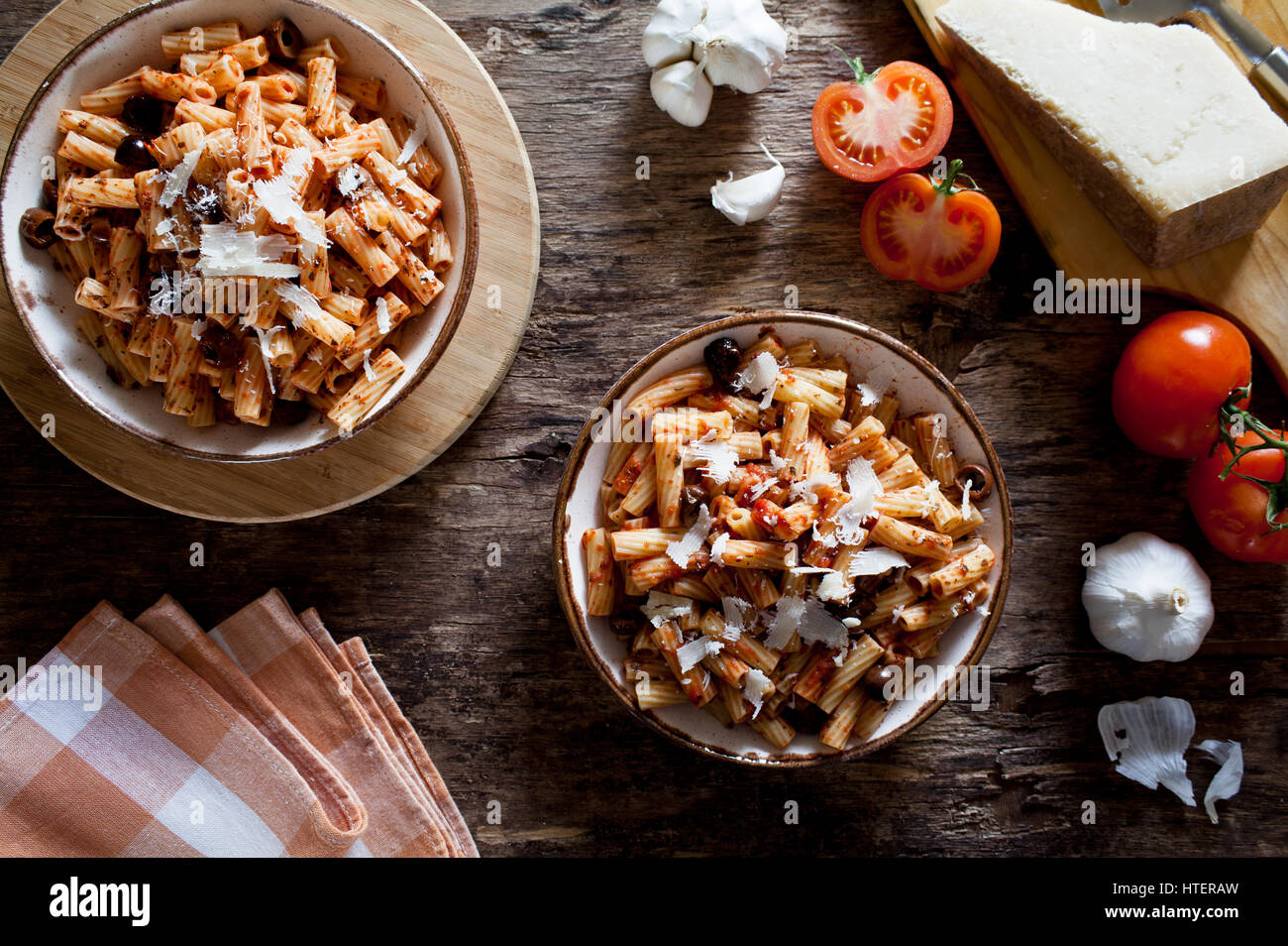 Couple of plates of rigatoni pasta with tomato sauce and olives Stock Photo