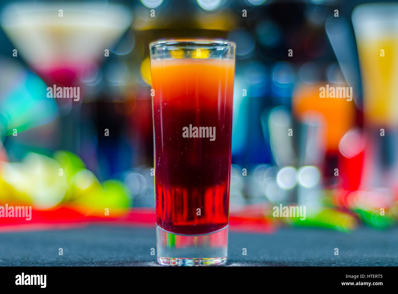 colored drink in glass for shots, a combination of orange with red, colorful background, drink shot - Stock Image
