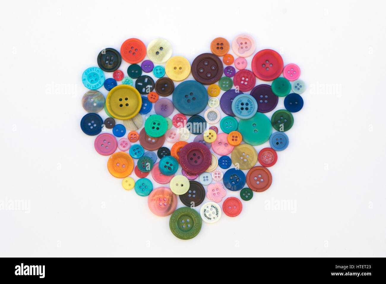 Assortment of colourful Buttons shaped as a heart on white background - Stock Image