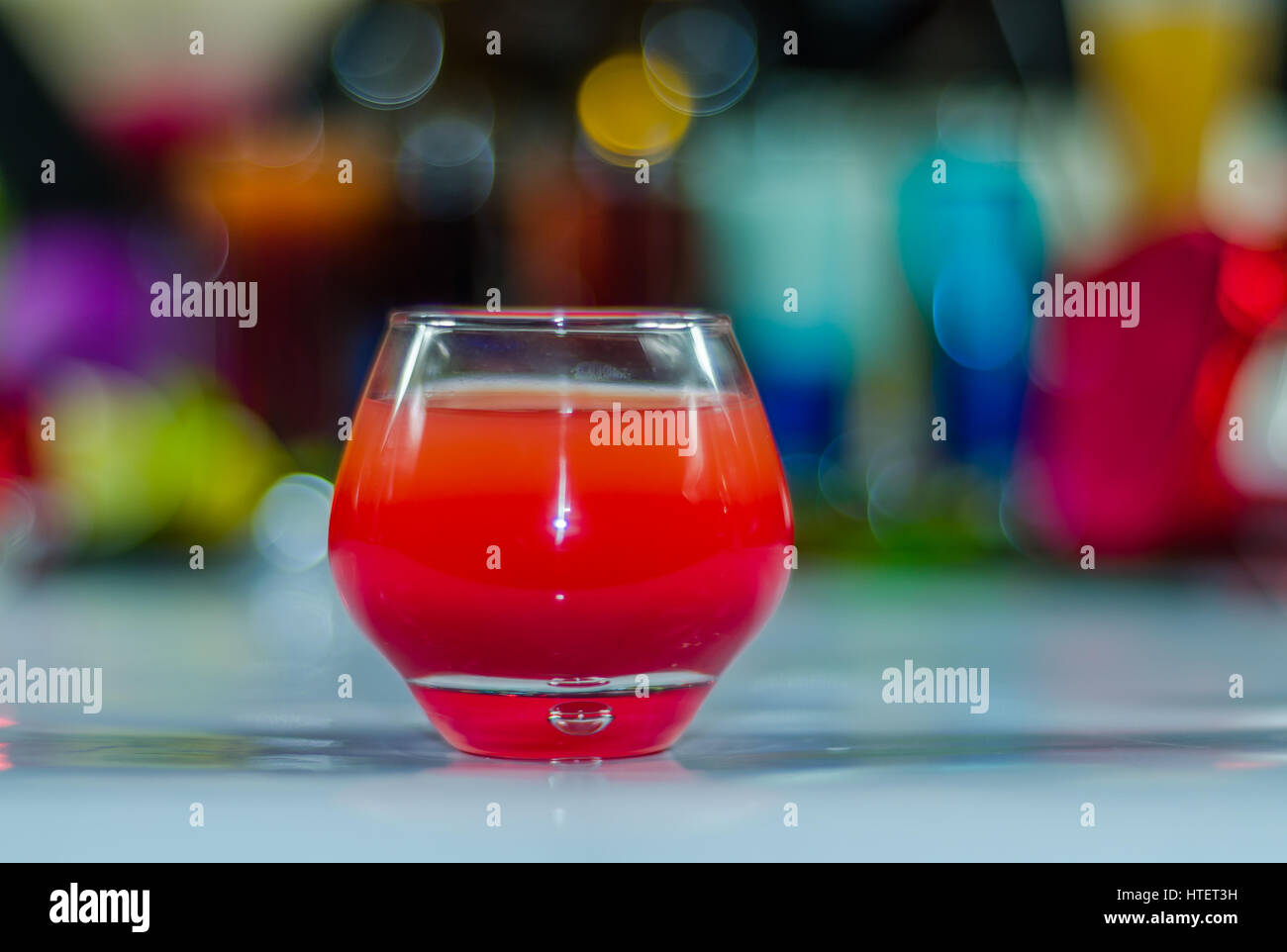 colored drink in glass for shots, a combination of red with violet, colorful background, drink shot - Stock Image