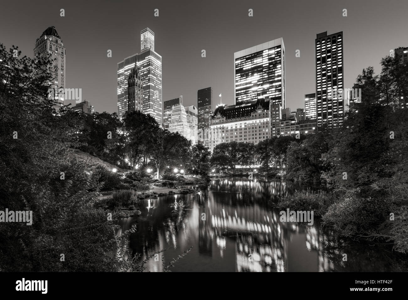 Midtown Manhattan skyscrapers illuminated in evening.The buildings of Central Park South are reflected in the Pond. - Stock Image