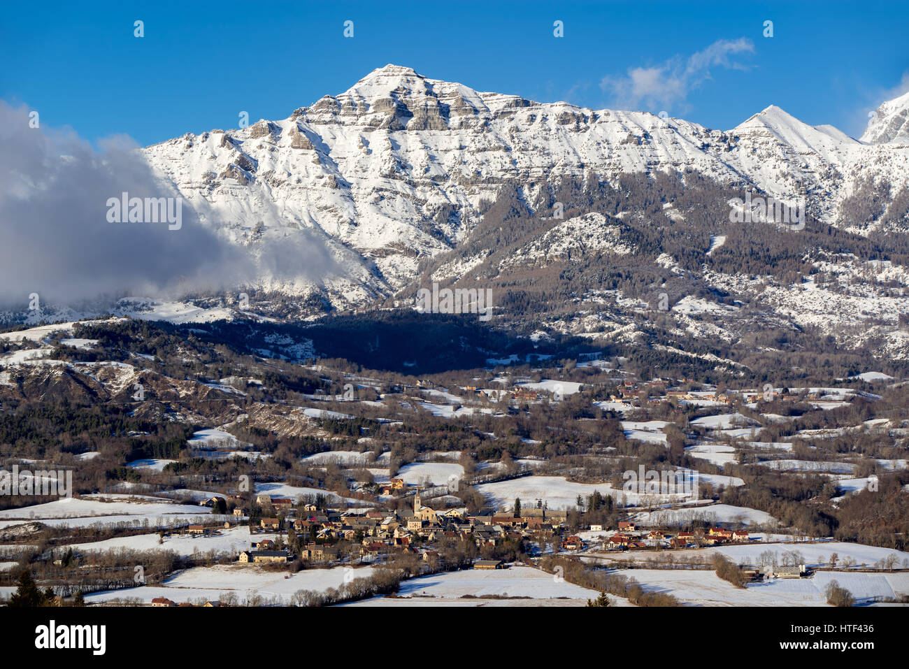 The village of Saint-Julien-en-Champsaur and the Queyrel Peak mountain in winter. Hautes Alpes, Southern French - Stock Image