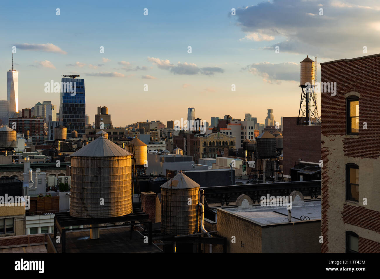 Chelsea rooftops in summer sunset light with high-rises, water towers and the World Trade Center in the distance. - Stock Image