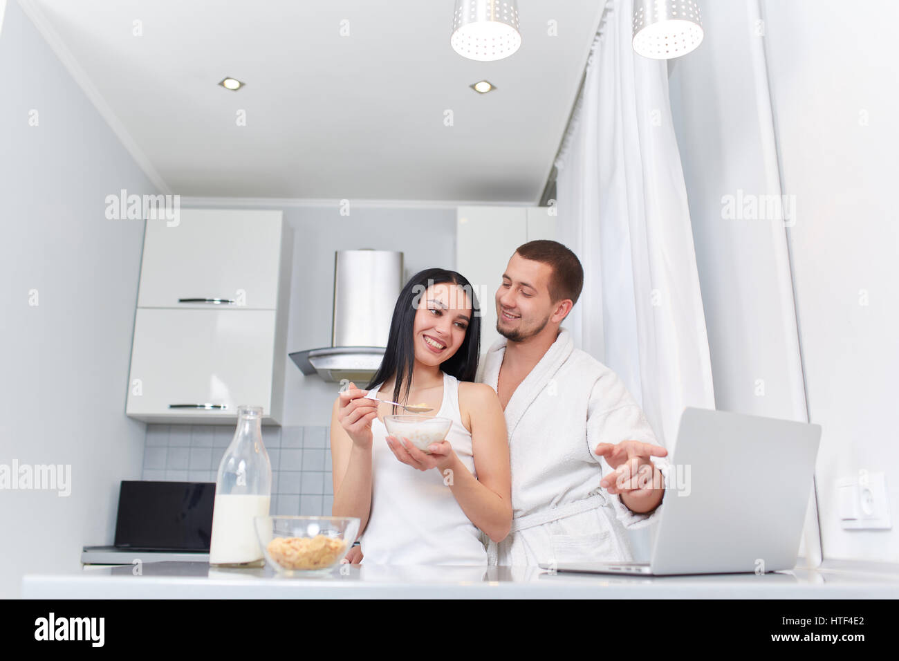 Couple discussing news and watching in laptop in morning at kitchen ...