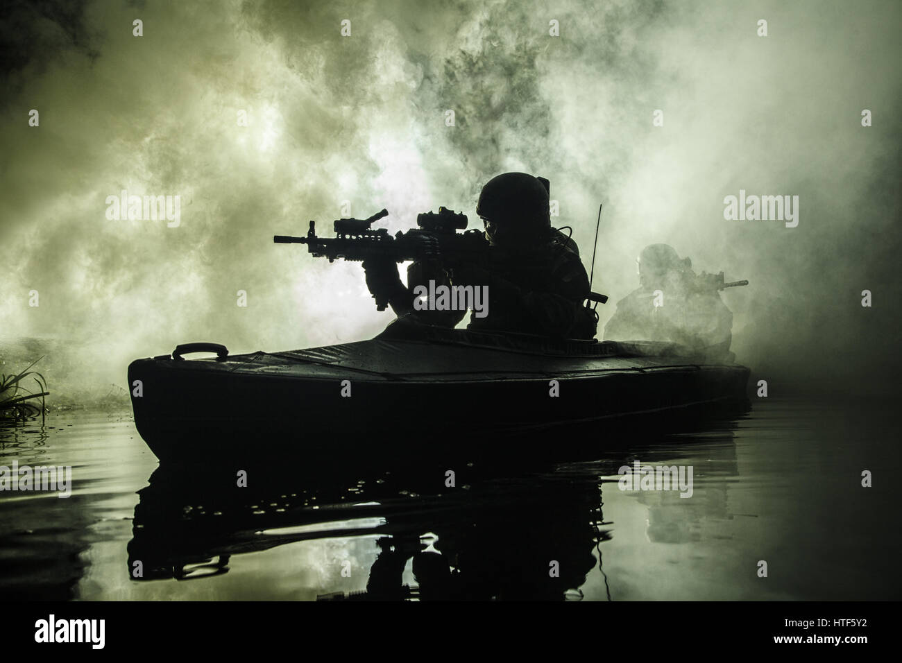 Backlit silhouette of special forces marine operators in military kayak on fire explosion background. Battle operation, - Stock Image