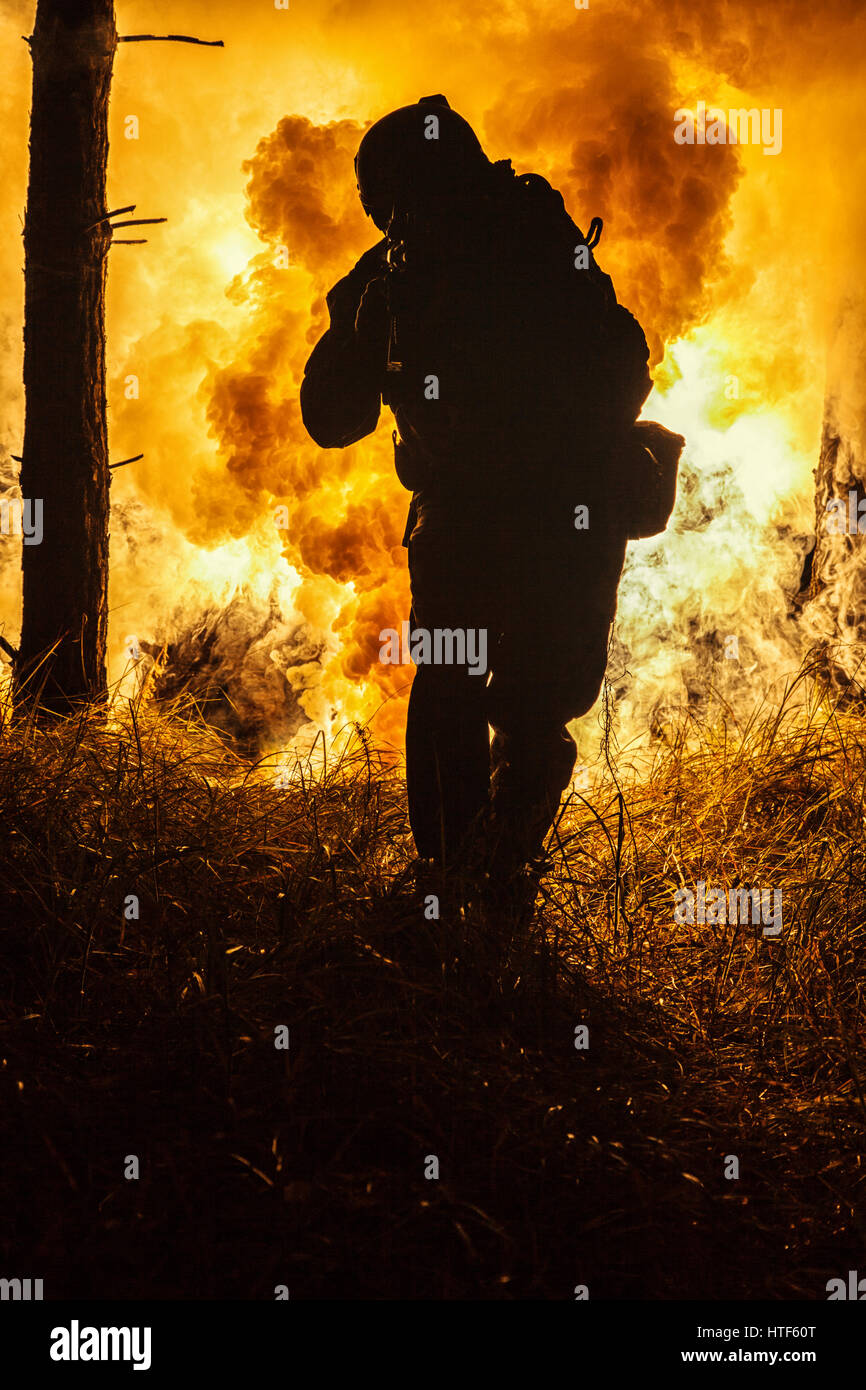 Backlit silhouette of special forces marine operator in forest on fire explosion background. Battle, bombs exploding, - Stock Image