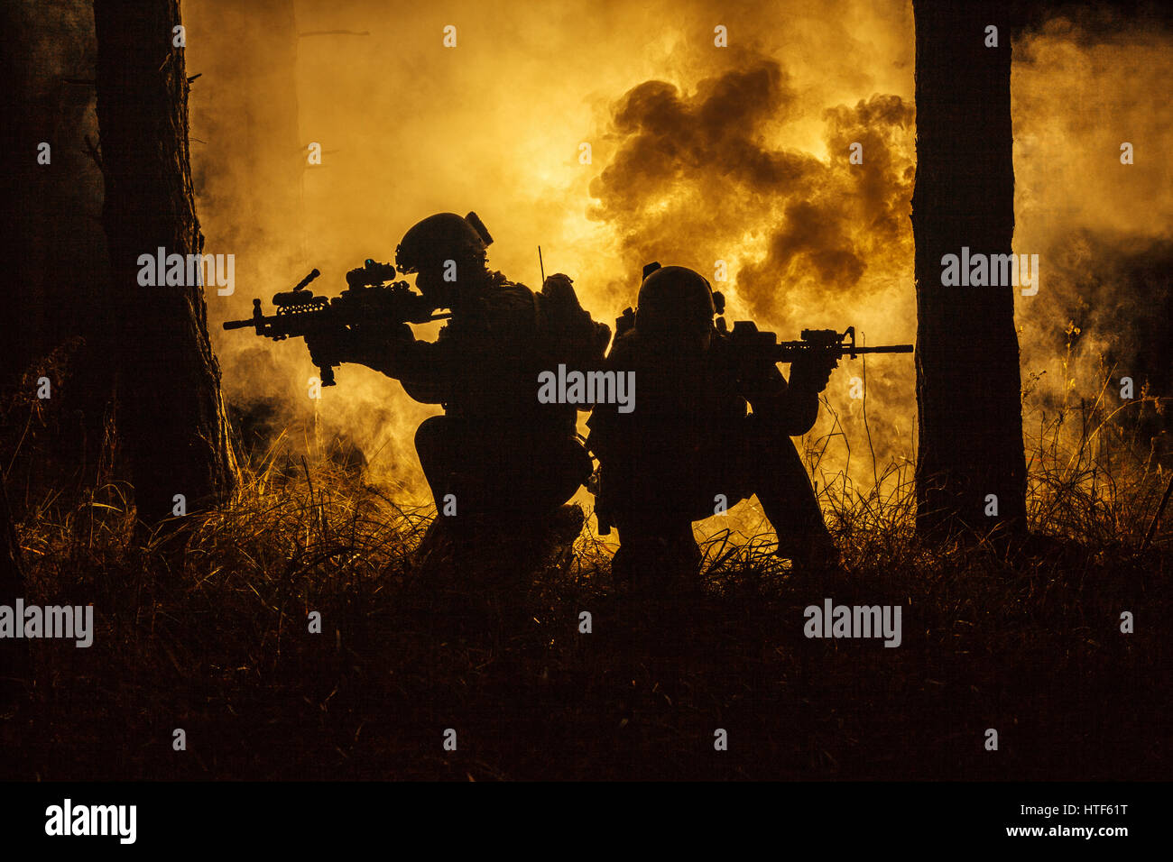 Backlit silhouette of special forces marine operators in forest on fire explosion background. Battle, bombs exploding, - Stock Image