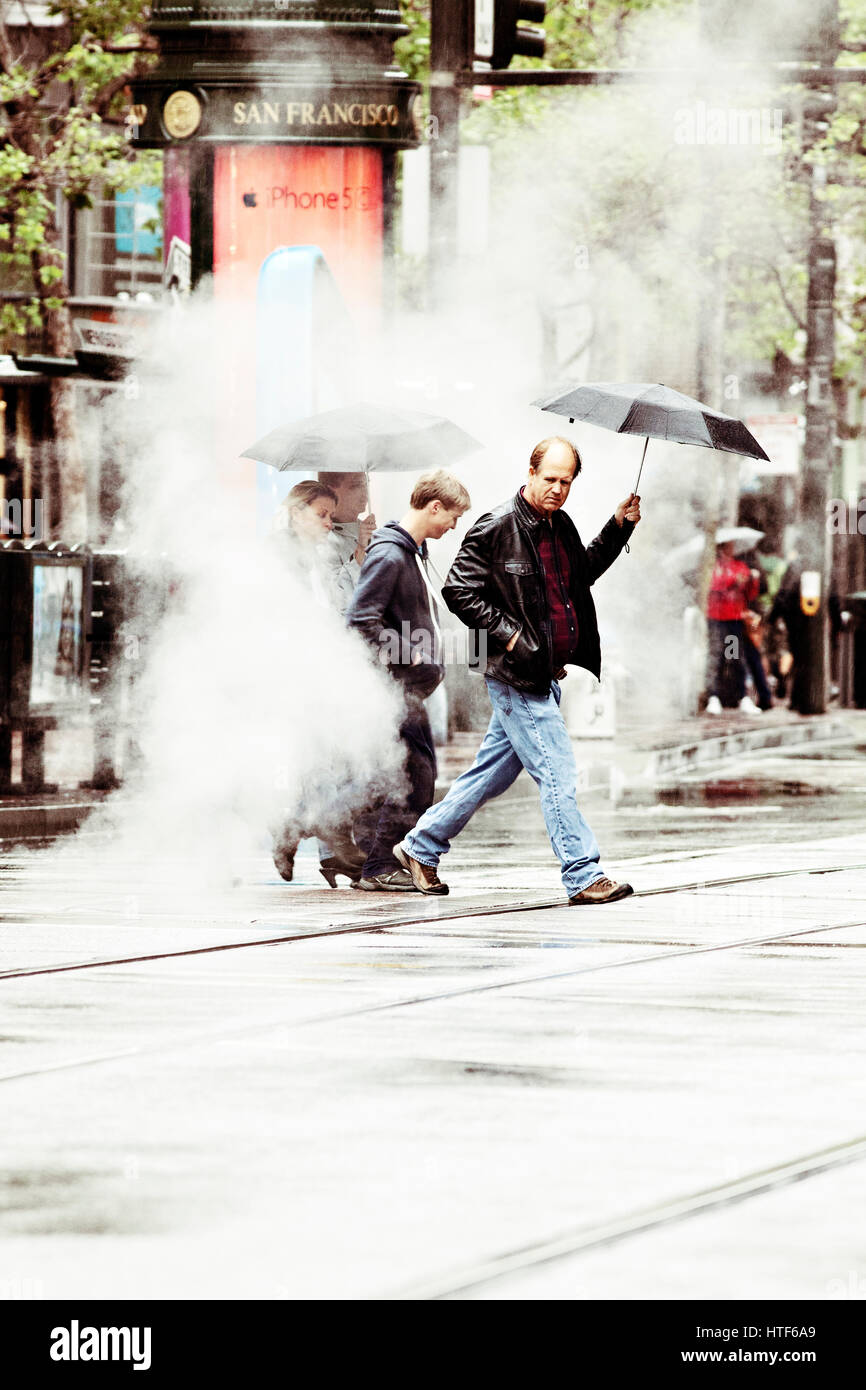 People walking through steam as they cross the street. San Francisco, California. - Stock Image