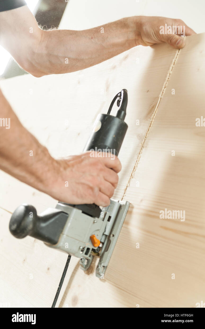 woodworker cutting down a piece of a wooden board using his saw and his powerful arms - Stock Image
