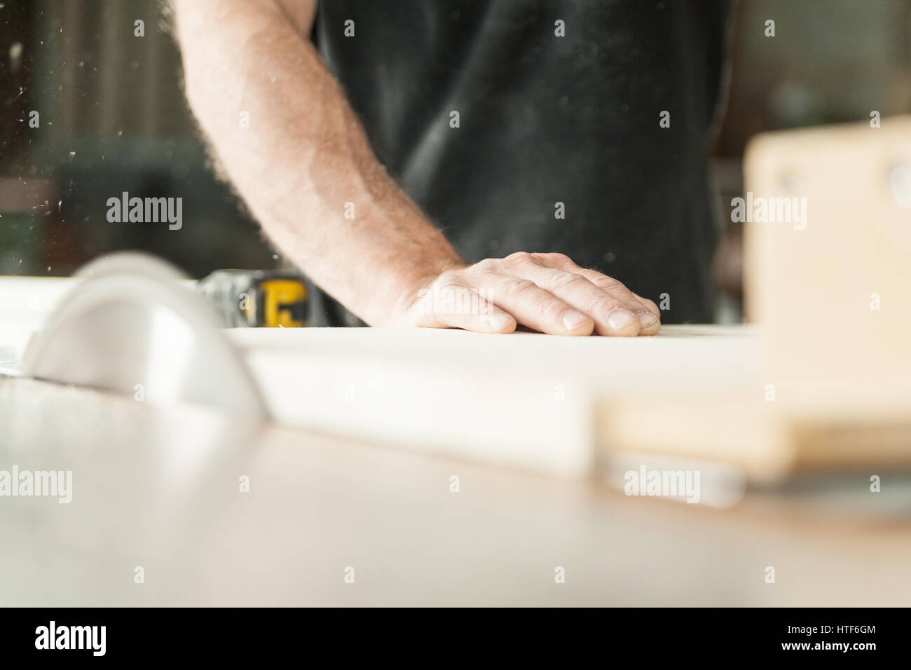 woodworker cutting down a piece of a wooden board using his circular saw and his powerful arms - Stock Image