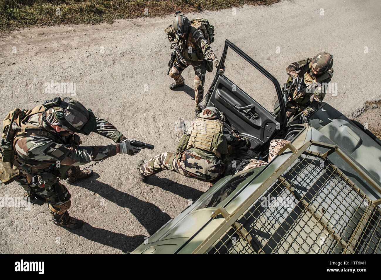 Squad of elite french paratroopers of 1st Marine Infantry Parachute Regiment RPIMA detaining terrorist in the car, - Stock Image