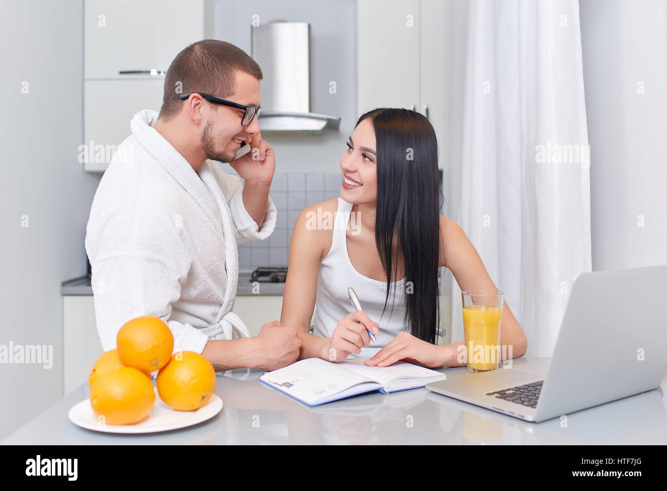 Brunette woman with long hair holding hand on chin and seriously looking at her husband. Boyfriend in glasses and Stock Photo