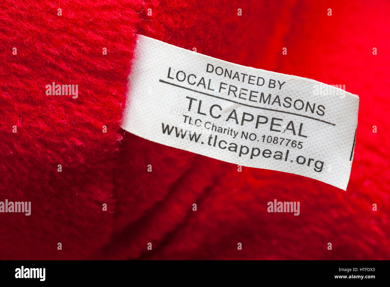 Donated by local Freemasons TLC appeal (teddies for loving care) label on soft cuddly toy - Stock Image