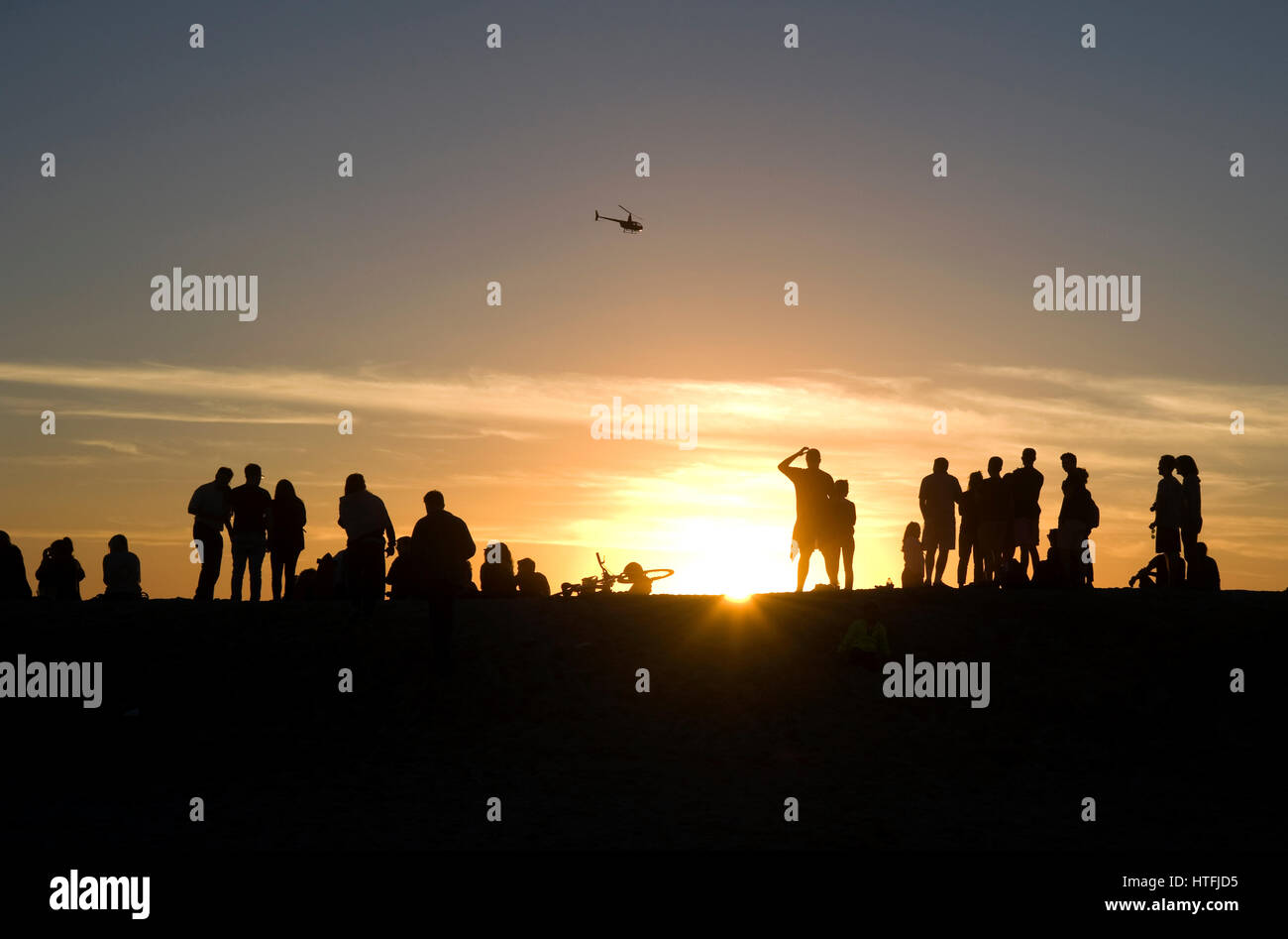 People watching the sunset at Venice Beach, California as a coast guard helicopter flies past. Stock Photo