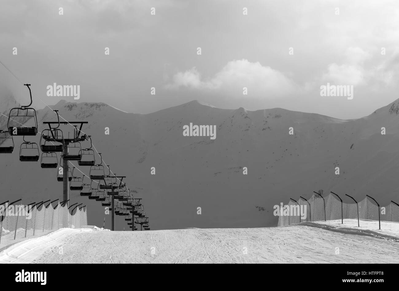 Black and white view on snow skiing piste and ropeway. Caucasus Mountains. Georgia, region Gudauri in evening. - Stock Image