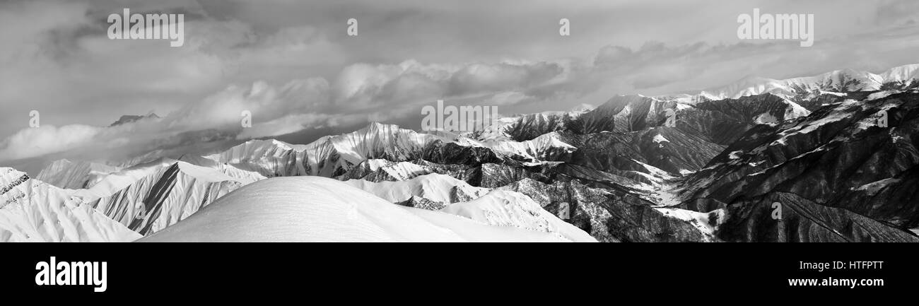 Black and white panorama of off-piste snowy slope and cloudy mountains. Caucasus Mountains, Georgia, region Gudauri - Stock Image