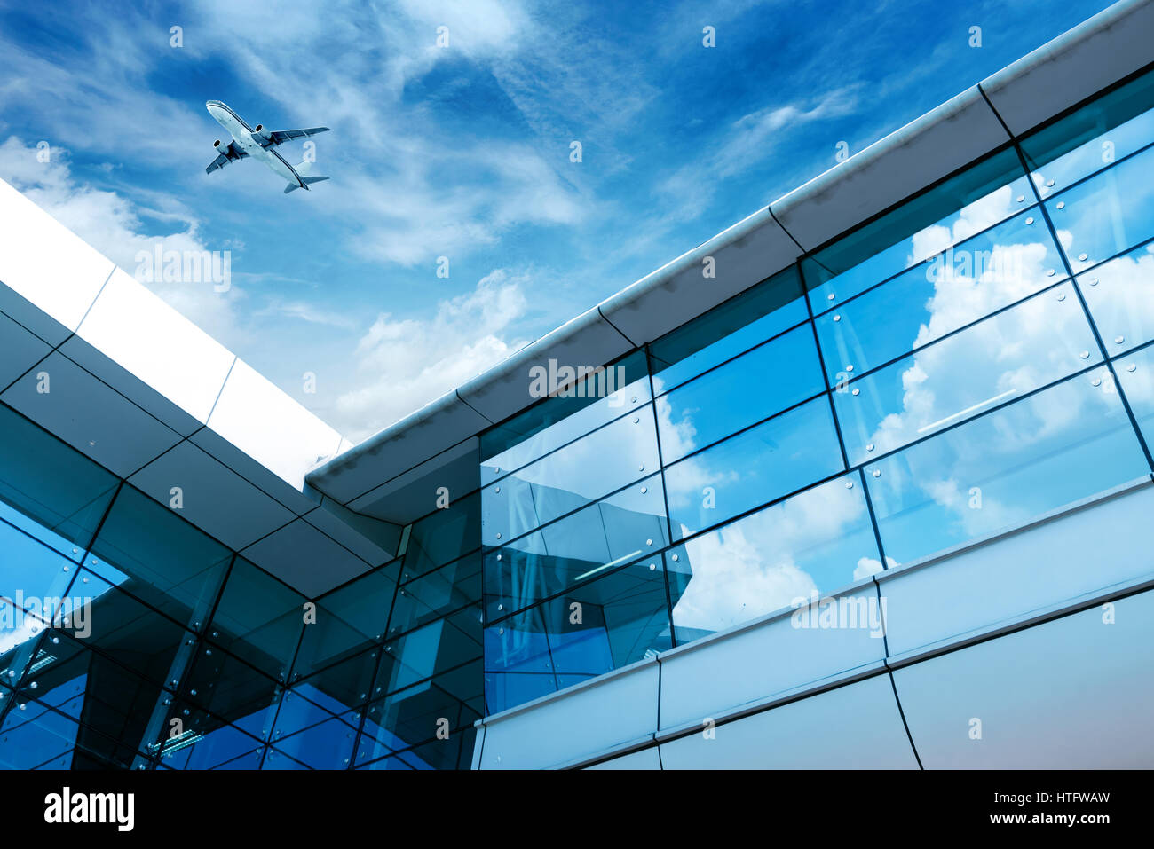 glass curtain wall and aircraft against a blue sky Stock Photo
