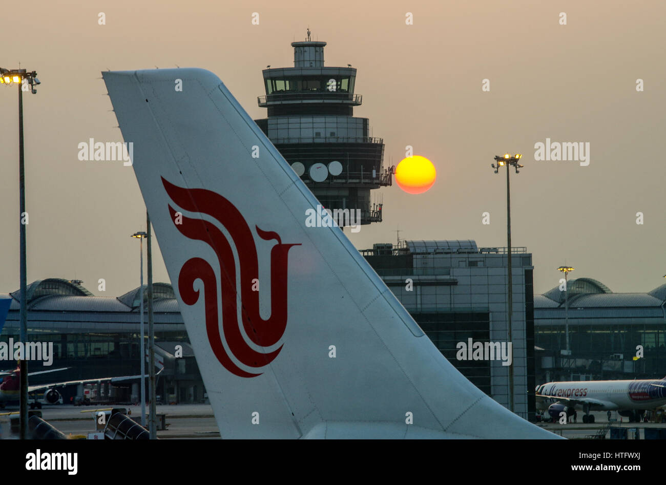 Sun setting behind the Air Traffic Control Tower in Hong Kong Chek Lap Kok Airport - Stock Image