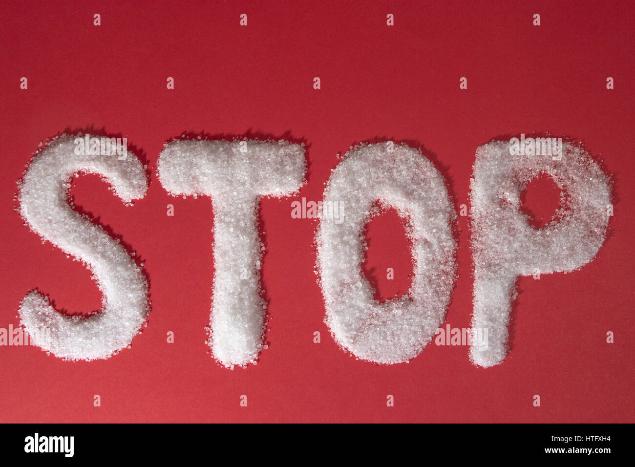 The word STOP written by sugar grains on red background. Top view - Stock Image