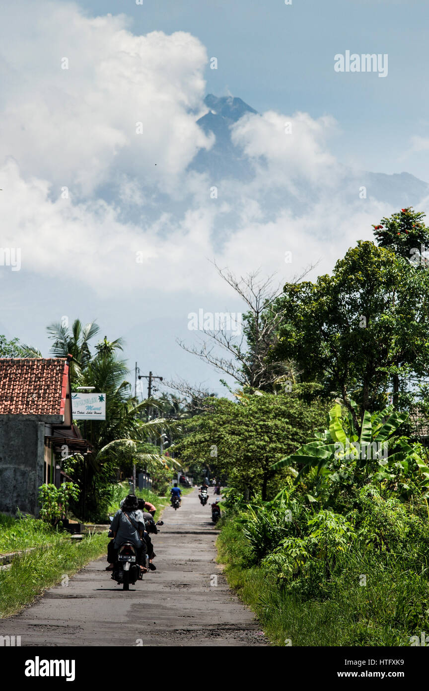 Gunung Merapi volcano towering over a village on the outskirts of Yogyakarta - Central Java, Indonesia - Stock Image